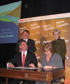 Minister of the Environment Jim Prentice and TCT Chair Valerie Pringle sign the MOU