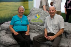 Longtime TCT donors and supporters Grace and Arnold Rumbold taking a load off on a decorative boulder that serves as a seating area in the first-ever indoor section of the TCT that just opened in Blackfalds, Alberta.