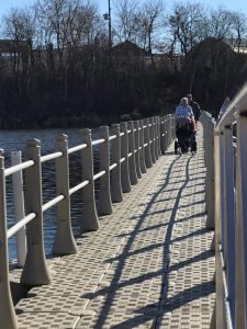 A wheelchair user using the improved boardwalk and enjoying views of the water in Yorkton, Saskatchewan.
