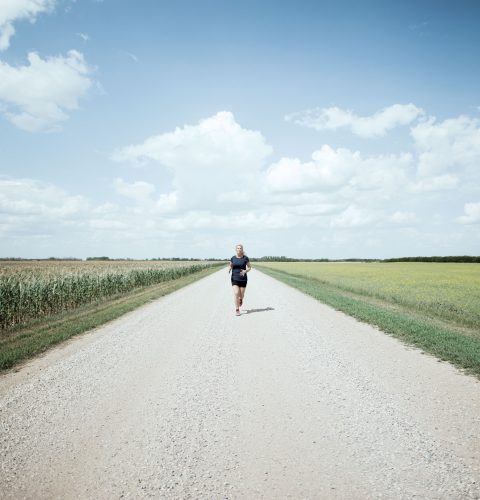 Karen Edwards runs along a wide road of prairie, with blue skies in the background and green grass on either side.