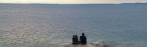 Dana Meise is sitting on a rocky beach looking at the horizon over the lake