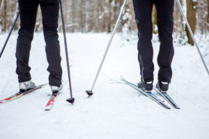 The legs and skis of two cross country skiiers who are skiing on a trail.