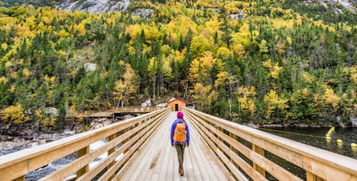 Woman walking down wooden bridge towards forest