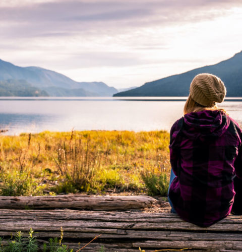 Woman looking at lake with mountains in the background