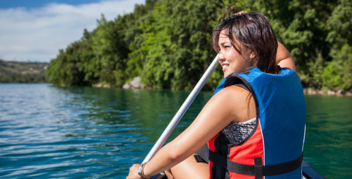 A woman in life jacket paddling on lake